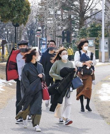 強い風を受けて服を押さえながら歩く人=20日午前11時半、金沢市広坂1丁目