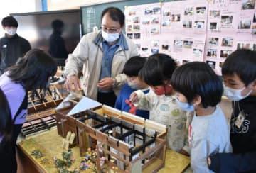 昔の住居をイメージした手作り模型を使い、通山小で授業を行った内田律夫さん(左から3人目)