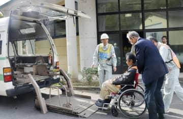 中国電力島根原発での事故を想定した総合防災訓練で、車いすのまま福祉タクシーに乗せられる要支援者役の参加者=2019年11月、松江市