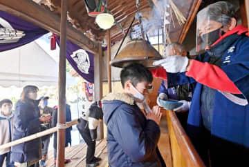 護摩炉をかぶせてもらうマスク姿の参拝者=2月20日、福井県鯖江市長泉寺町2丁目の天台宗中道院