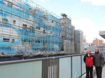 JR岐阜駅北口に向かって建つ集合ビルの南側壁面に描かれている空と雲。事業に関わる守富寛さん(左)と汲田義明理事長=岐阜市問屋町