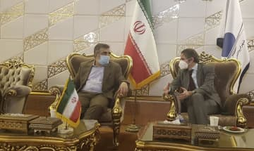 テヘランの空港でイラン原子力庁の関係者と談笑するIAEAのグロッシ事務局長(右)=20日(イラン原子力庁提供・AP=共同)