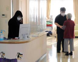 フェースシールドをして高齢者を介助する職員。クラスターの発生後に感染防止策を強化した=西宮市、神港園レインボー西宮