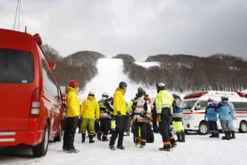 雪崩が発生した八甲田スキー場周辺に集まる消防隊員ら=21日午後3時24分、青森市