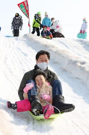 巨大な雪の滑り台でそり滑りを楽しむ子どもや親子=21日、長岡市千秋3