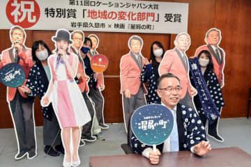 授賞式にリモートで参加する遠藤譲一市長(手前)と市観光交流課の職員