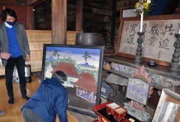 尾高惇忠筆の奉納額(右上)と藍染め絵馬を来場者に説明する山下祐樹さん(左)=21日、熊谷市下川上の宝乗院愛染堂