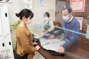 無料クリーニングに持ち込まれた学生服を確認する福田尚史社長(右)=山鹿市