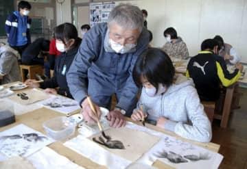 【児童が描いた墨絵の指導をする宮崎氏(中央)=亀山市両尾町の市立野登小学校で】