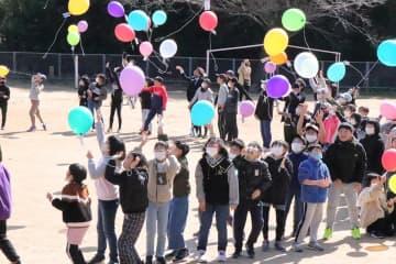運動場で風船を飛ばし、旧校舎に別れを告げる児童=松浦市立鷹島小