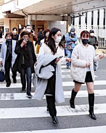 季節外れの暖かさに、上着を脱いで歩く人たちの姿も=22日、JR大阪駅前