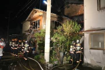 全焼した民家で消火活動する消防士たち(23日午前2時33分)