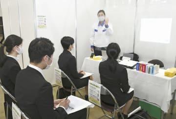 企業の担当者から説明を受ける学生=2月23日、福井県産業会館