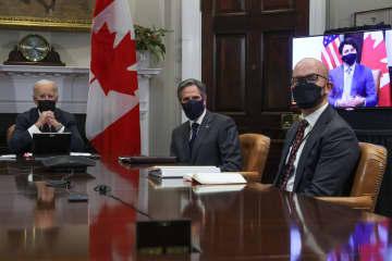 カナダのトルドー首相(右端モニター内)とホワイトハウスでバーチャル形式の首脳会談を行うバイデン大統領=23日、ワシントン(ロイター=共同)