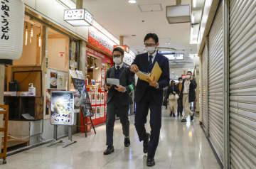 「まん延防止等重点措置」の対象期間に入りJR大阪駅近くで飲食店などの状況を確認する「見回り隊」=5日午後