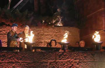 7日、エルサレムで開かれたユダヤ人大量虐殺の犠牲者追悼式典で、火をともす生存者ら(共同)