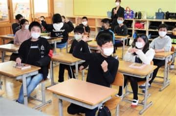 教室であった始業式。担任教諭の発表があり、笑顔をみせる6年生児童たち=8日、南阿蘇村