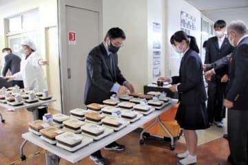 8日から始まったデリバリー型の給食を受け取る生徒ら=横浜市立上飯田中学校
