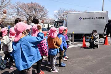 出発式で手を振って給食配送車を見送る子どもたち=長井市給食共同調理場