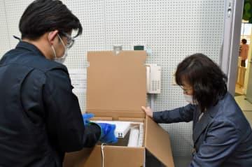青森市保健所に届いたワクチンを慎重に箱から取り出す職員ら=8日午前9時50分ごろ