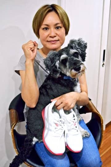 愛犬のミニチュア・シュナウザーのこたつ君に「頑張って走ってくるね」と決意を語る玉城聡美さん=29日、沖縄市
