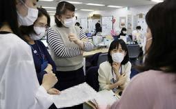 受け入れ先の病院と調整を続ける保健師ら。時折集まり相談を繰り返す=27日午後、神戸市役所(画像を一部加工しています)