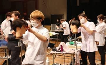 制限時間内にマネキンの頭髪を整えるため、手際よくはさみを操る参加者たち(京都市左京区・京都教育文化センター)