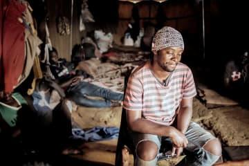 南アフリカの国境の町のシェルターで過ごす移民の男性 長期間留め置かれる人びとも多い=2019年 © Luca Sola
