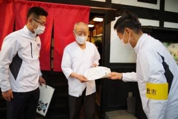 飲食店の店主(中央)に感染予防対策チェックシートを配り、徹底を促す倉敷市職員