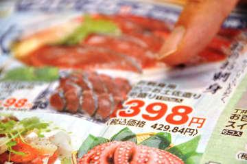 ある県内スーパーのチラシ。赤い太字の「本体価格」と、細く黒い字の「総額」を男性が指し示す