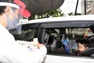「ドライブスルーじどうかん」で絵本などを児童館の職員(左)から受け取る子ども=4月28日午前、松山市若草町