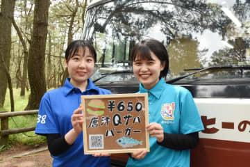 唐津Qサバとからつバーガーのコラボバーガーを発案した永野悠希さん(左)と山崎瑞季さん=唐津市の虹の松原