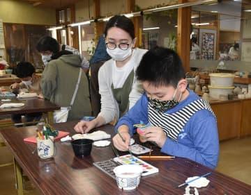 陶芸工房で本焼きしたかぶとの陶器に色付けする親子=板柳町ふるさとセンター「工芸館」
