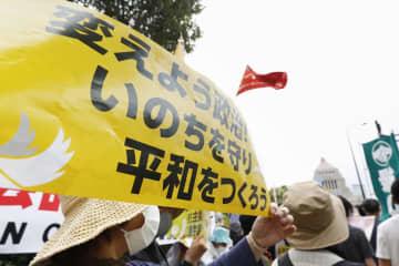 国会前で開かれた護憲派の集会でメッセージを掲げる参加者=3日午後