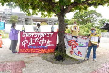 聖火リレー会場の前で抗議の横断幕を掲げる人々。警備員や運営スタッフが遠巻きに見守る=5月1日午後2時11分
