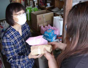 来場者(右)に生理用品を手渡すハーモニーネット未来のスタッフ(笠岡市)