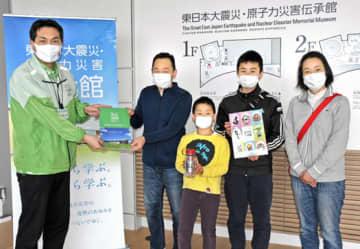小林副館長から記念品を受ける伊東さん(左から2人目)家族