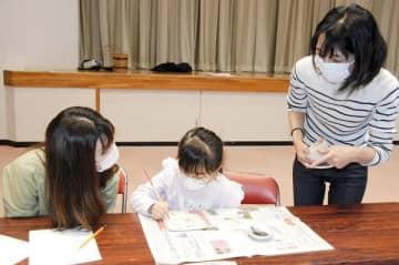 【倉岡さん(右端)の指導で絵付けをする子ども=亀山市東御幸町の市文化会館内中央コミュニティセンターで】