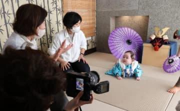 こどもの日を前に、マスク姿のスタッフにあやされながら初節句の記念撮影をする赤ちゃん=4日午後、宮崎市新別府町・ワタナベフォトスタジオ一ツ葉