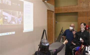 オンライン交流会で、新潟からの呼び掛けに応える胎児性水俣病患者の金子雄二さん(右)=4日、水俣市