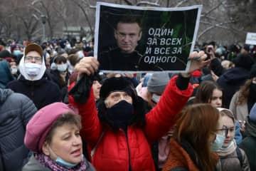 ロシア・ノボシビルスクで行われた抗議デモで反体制派ナワリヌイ氏の写真を掲げる人=4月21日(タス=共同)