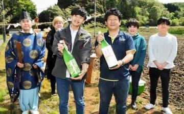 完成した日本酒「初酔」を手に笑顔を見せる丹野社長(右)、広瀬さん(左)とプロジェクトのメンバーら
