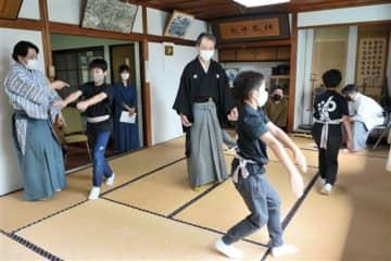 狂言師の指導を受けながら新作狂言の練習をする子どもたち=熊本市中央区