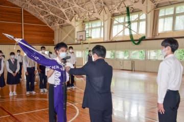 清川和幸校長(中央)に団旗を返納する森脇丈さん