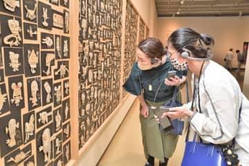 ヘッドホンで音声ガイドを聞きながら作品を鑑賞する来場者=10日、鳥取市の鳥取県立博物館