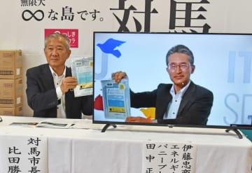 対馬の海洋プラスチックごみを原料の一部に開発したポリ袋を掲げる田中執行役員(右)と比田勝市長=対馬市役所