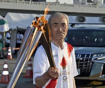 トーチキスで自らのトーチにしっかり聖火を引き継ぐ野田さん=10日午後5時50分