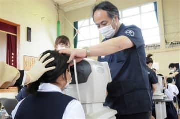 河内小・中の児童・生徒の目の状態などを専用機器を使って調べる県視能訓練士の会の冨士登謙司会長=熊本市