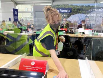 G7サミットの国際プレスセンターで、机を消毒する清掃係のレベッカ・プロバートさん=10日、英コーンウォール(共同)