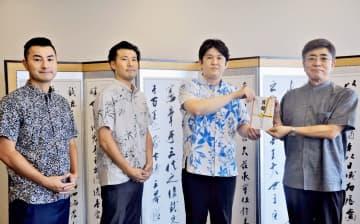 本社の瑞慶山秀彦専務(右)に寄付金を手渡す青い海の屋嘉比元常務(右から2人目)ら=10日、沖縄タイムス社